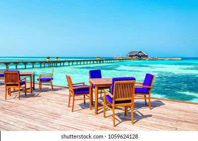 An exotic view of a wooden restaurant on stilts on a background of azure water and sunny blue sky