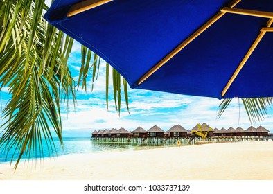 Exotic wooden houses on the water and palm leaf with sun umbrella in the foreground