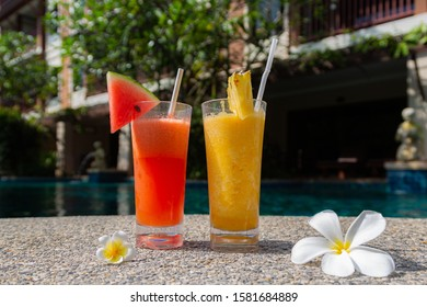Exotic yellow and red fruitcocktails placed in the sun behind a little flower at the edge of a swimmingpool.