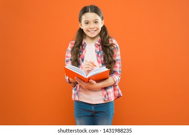 Expand your mind, read a book. Small child reading book on orange background. Little girl holding text book. Interesting book story for kid.