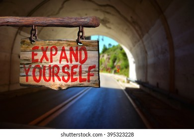 Expand yourself motivational phrase sign on old wood with blurred background
