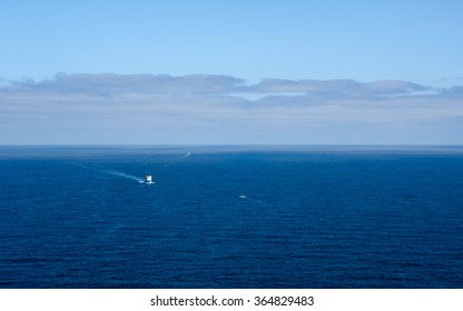 Expansive deep blue ocean seascape with three boats in distance, under layer of clouds forming against sky on horizon.