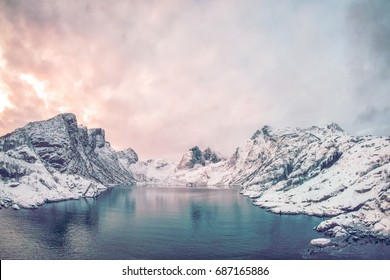 Expansive fjord in the Lofoten Islands Norway surrounded with snowy mountains and a colorful winter sunset.
