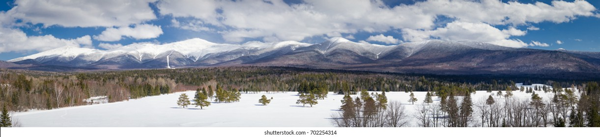 An expansive panorama of a beautiful winter view of the Presidential Mountain range with a clear view of the Mount Washington summit in New Hampshire