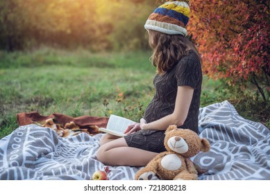 An expectant mother with a tummy sits on a blanket with a toy bear and reading stories to the baby in a beautiful autumn Park. The concept of pregnancy and the autumn harmony