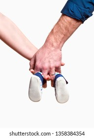 Expecting Couple with Hands Holding Baby Shoes.