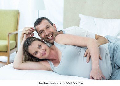 Expecting couple lying on bed in their bedroom