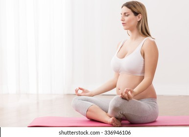Expecting mom doing yoga exercise in pregnancy