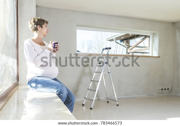 Expecting woman resting on building site in the new house