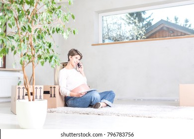 Expecting woman sitting on floor during relocation making a phone call