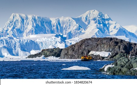 Expedition members traveling in a zodiac in Antartica