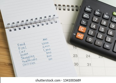 Expense and budget concept, list of expense in small notepad and calculator on desktop calendar on wooden table.