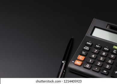 Expense, cost, budget and tax or investment calculation, black pen with calculator on dark black background table with blank copy space.