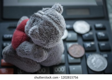 Expenses for the child, payments, alimony. On the calculator coins and children's toys. Top view, vignetting, background blurred.