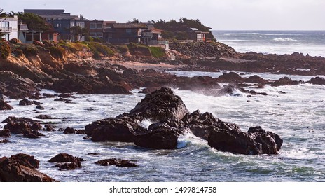 expensive beach homes sit dangerously close to the edge of a cliff above a rocky beach on the pacific coast near cambria in california