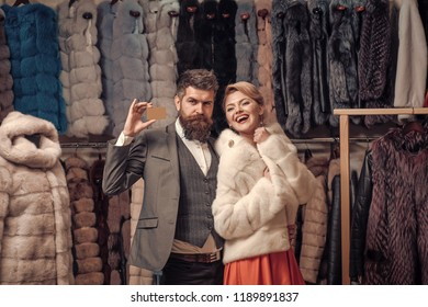 Expensive clothes and money concept. Couple shopping in fur mall. Woman in white fur coat with bearded macho looking for new overcoat holding credit card. Girl with happy face wearing white mink fur.