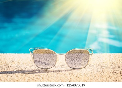 Expensive fashionable sunglasses with metal arms in the bright rays of the sun