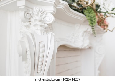 Expensive interior. Stucco elements on light luxury fireplace. White patterned. Mouldings element from gypsum. Roccoco style