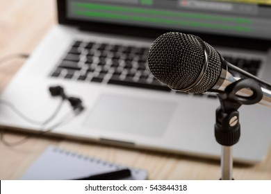 Expensive microphone in the foreground of the camera connected to a holder. Modern laptop and headphones in the blurred background.