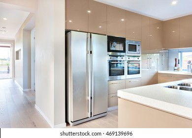 Expensive and modern kitchenware including silver color and tall two door refrigerator and four ovens and stoves fixed to the wall with cabinets around it. There is a ceramic counter top with the sink