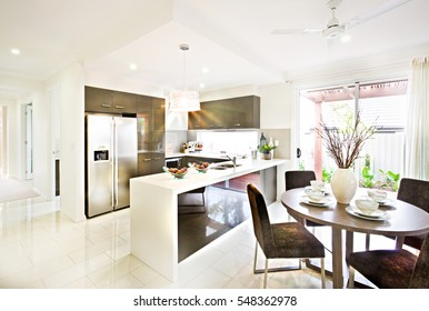 Expensive and modern kitchenware including silver color and tall two door refrigerator and four ovens and stoves fixed to the wall with cabinets around it. There is a ceramic counter top.