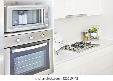 Expensive oven design with kitchen ware, cooker close up at room, perfect lightning, evening time photograph,  also some glass bottles on pantry table.