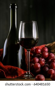Expensive red wine, glass, grapes. Beautiful black background. Old wood