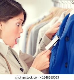 Expensive shopping prices in euro. Woman shopper shocked and surprised over high clothes retail prices in clothing store. Funny image of multicultural young woman.