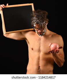 Expensive water tariff. Lack of water. Need take shower. Man naked body blackboard copy space. Macho attractive nude guy show blackboard. Man bearded tousled hair covered with foam hold piggy bank.