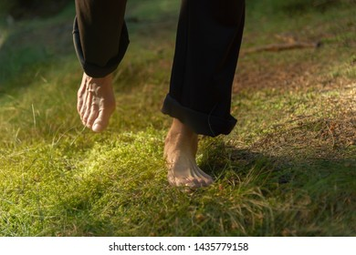 Experience the forest while bathing in the forest (Shinrin Yoku) with all your senses. The bare feet of a woman are walking carefully on soft moss. The sun warms the forest floor.