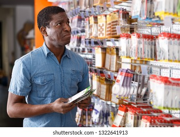 Experienced African American foreman looking for construction supplies for renovation works in building hypermarket