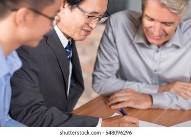 Experienced Asian man arranging merger deal