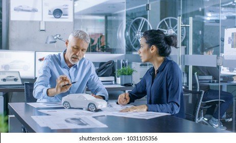 Experienced Automotive Designer and Female Engineer Works with a Concept Car Prototype Model, Perfecting it and Making Design Corrections. They Work in a Stylish, Bright, Modern Office.