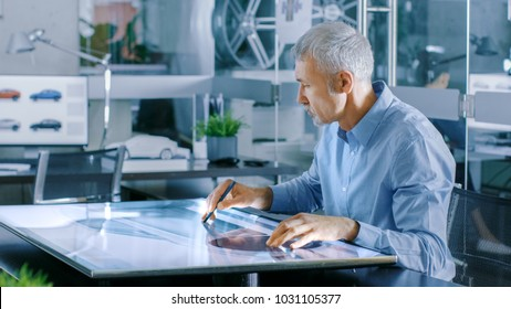 Experienced Automotive Designer Works With Digital Display Graphics Tablet Touschreen Table, Drawing Sketch of a New Car Prototype.
