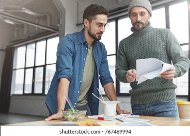 Experienced bearded male worker wears fashionable knitted clothes shows result or figures to unexperienced colleague, asks make calculation, spend working day in cabinet, have lunch, eat healthy food