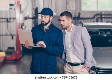 Experienced  bearded  specialist in cap demonstrating the damages of businessman`s car, showing the way of car repairing to client  on his device in workstation