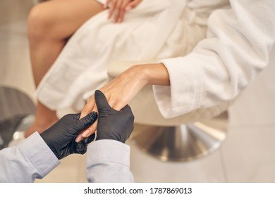 Experienced beauty parlor employee massaging female hand while spreading body lotion