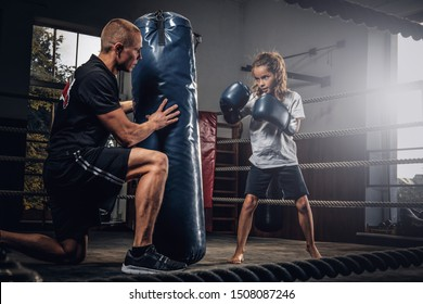 Experienced boxer trainer is training new little girl boxer for special competitions using punching bag.