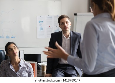 Experienced business coach rear view talking with diverse multiracial company members executive manager help interns improve knowledge at group training in office room. Mentoring and education concept