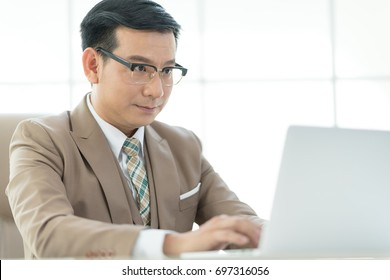 Experienced businessman or lawyer sitting work on laptop computer in the office.