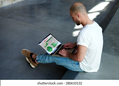 Experienced businessman looking at financial data with graphics and charts while work on a laptop computer, young entrepreneur working with graphs on his notebook,stylish hipster analyzing performance