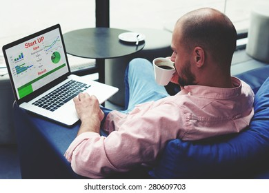 Experienced businessman sitting front laptop computer with financial information as graphics and charts, young entrepreneur work on notebook drinking cafe of cup while he sitting in modern coffee shop