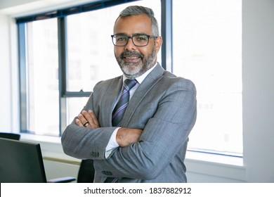 Erfahrener Geschäftsmann, der im Büro steht und die Kamera anschaut. Indischer Content Office Mitarbeiter in Brillen lächeln und posieren mit gefalteten Händen. Geschäfts-, Management- und Firmenkonzept