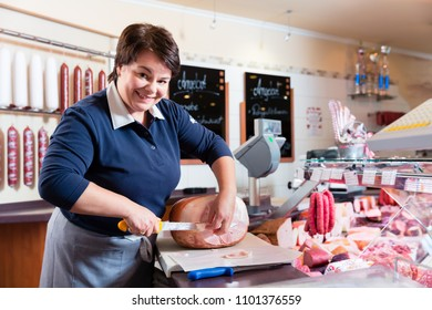 Experienced butcher shop assistant cutting ham to sell it