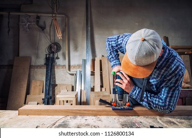 Experienced carpenter in work clothes and small buiness owner  is carving a wooden board on an  modern  hand drill in a light workshop side view, in the background a lot of tools