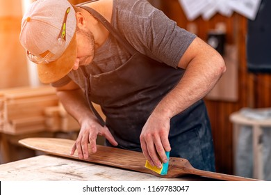 Experienced carpenter in work clothes and small business owner working in woodwork workshop,  using sandpaper for polishing children's helicopter blades at worktable in workshop