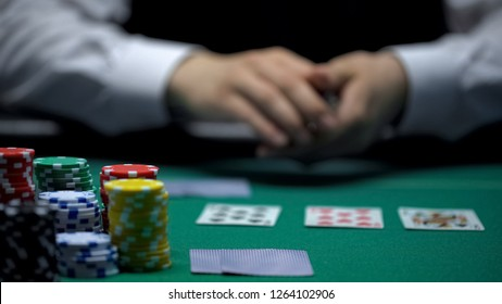 Experienced casino croupier dealing cards in poker game, gambling, close-up