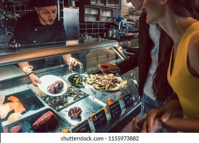 Experienced chef choosing raw seafood from the freezer for two customers in a trendy restaurant or cafeteria with fresh food