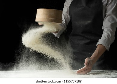 An experienced chef in a professional kitchen prepares the dough with flour to make Italian Italian pasta. concept of nature, Italy, food, diet and biology. on a dark background
