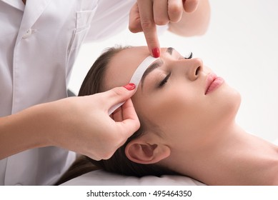 Experienced cosmetician pulling out brows